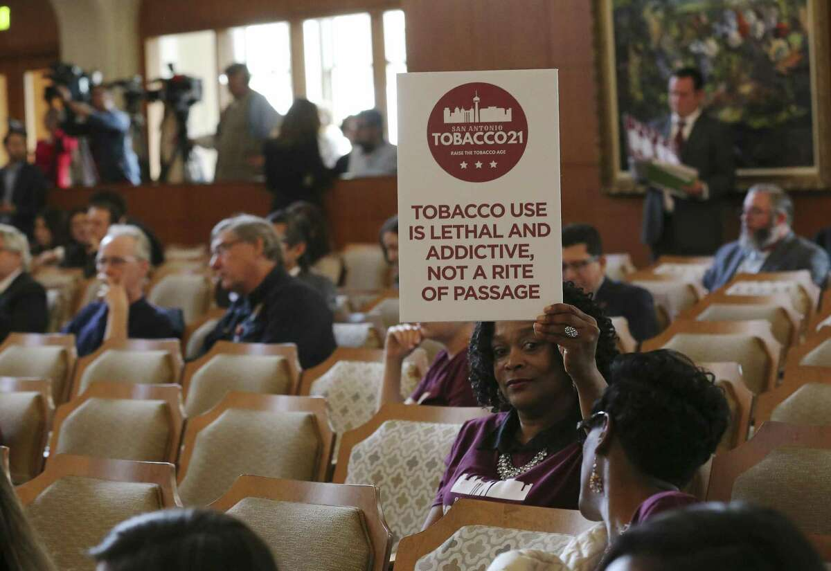 """A supporter of the city's new """"Tobacco 21"""" law holds a sign in City Council chambers warning of the dangers of tobacco use. City Council voted 9-2 in favor of a law prohibiting merchants from selling tobacco products to customers 18 to 20 years old. San Antonio is the first city in Texas to pass such a law."""