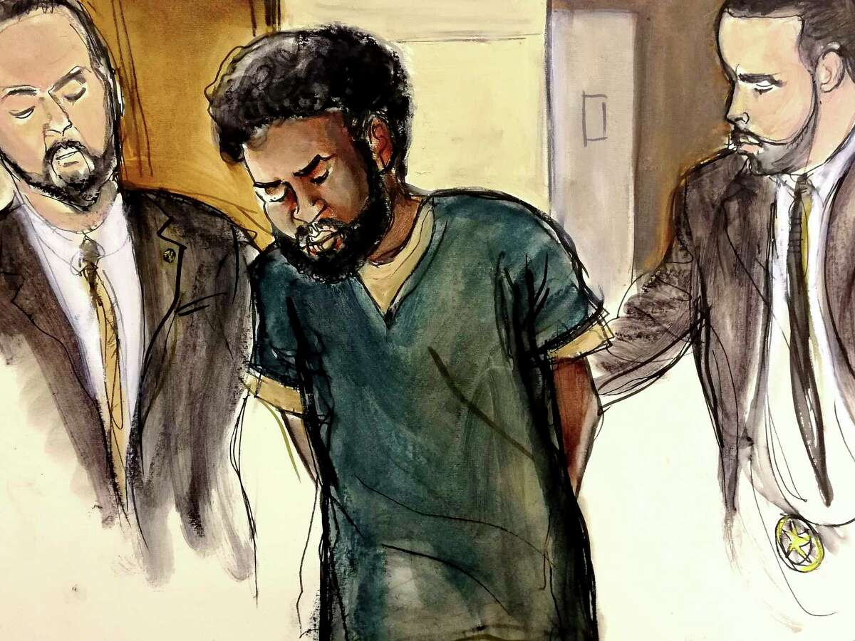 In this court room drawing, U.S. Marshals escort defendant Akayed Ullah, center, into court for his arraignment on charges that include providing material support to a terrorist organization and using a weapon of mass destruction, Thursday, Jan. 11, 2018 in New York. On Dec. 11, 2017, authorities say that Ulla detonated a pipe bomb on his person in a corridor linking the subway to the Port Authority bus terminal in New York City. (Elizabeth Williams via AP)