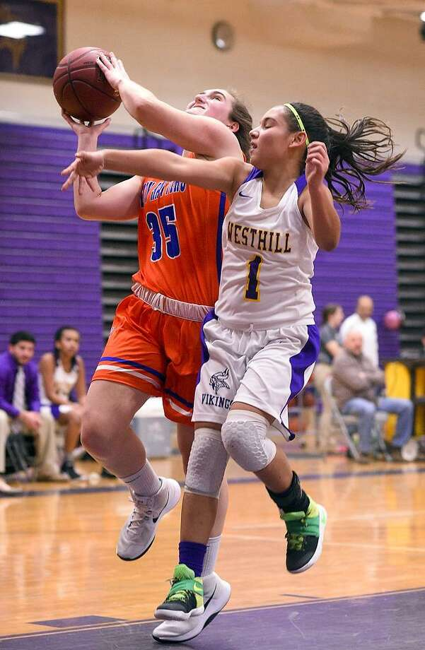 Danbury's Emily Grenier (35) is fouled on her shot by Westhill's Maddy Bautista (1)during a FCIAC girls basketball game at Westhill High School in Stamford, Conn. on Thursday, Jan. 11, 2018. Photo: Matthew Brown / Hearst Connecticut Media / Stamford Advocate