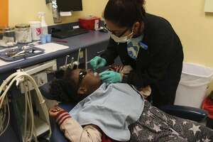 Ruby Ayala prepares Kourtnee Thomas, 8, for an extraction during a free dental clinic at Kool Smiles General Dentistry for Kids, Sunday, May 21, 2017. The company was fined by the Department of Justice Thursday.