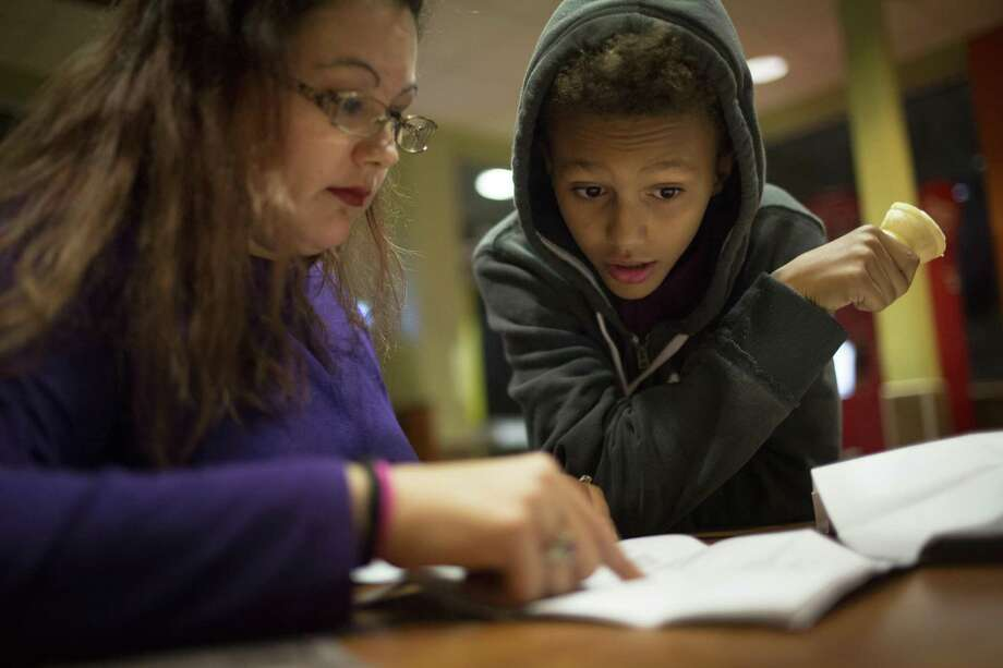 Nicole Rechner, 33, revises a math quiz with her son Demarcus Fuller after eating dinner. Fuller scored 47 percent on the quiz, and his mother is trying to explain to him how he could had succeeded on the quiz in this 2016 photo. On Thursday, Rechner wept when she learned a U.S. Department of Education investigation had determined that Texas Education Agency officials illegally led school districts across Texas to delay or deny special education services to students by setting an arbitrary cap on services. Photo: Marie D. De Jesus /Houston Chronicle / Stratford Booster Club