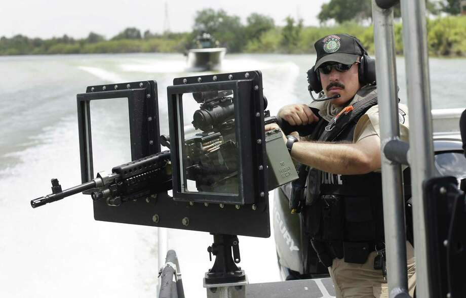 A Texas Parks and Wildlife warden with a .30-caliber machine gun patrols on the Rio Grande near Mission in this 2014 photo. With the Trump administration reportedly poised to whack federal spending on border security so it can build a border wall, Democratic gubernatorial candidate Andrew White on Thursday proposed cutting the $800 million the state spends for border security. Photo: New York Times File Pool Photo / POOL
