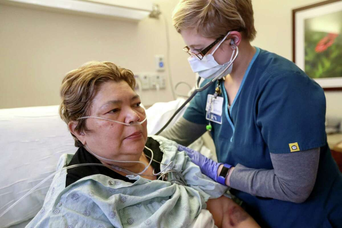 Jennifer Brown, right, a nurse, listens to the lungs of Sara Jimenez, a flu patient, at Houston Methodist Hospital, Thursday, Jan. 11, 2018, in Houston.