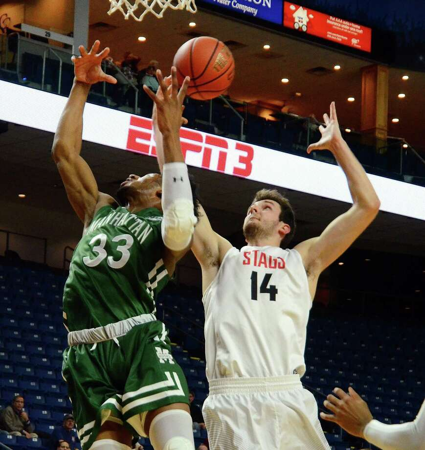 Fairfield University's Matija Milin (14) tries to grab a reboundover Manhattan College's Pauly Paulicap during their game Thursday night at the Webster Bank Arena in Bridgeport. Manhattan won 59-53. Photo: Christian Abraham / Hearst Connecticut Media / Connecticut Post
