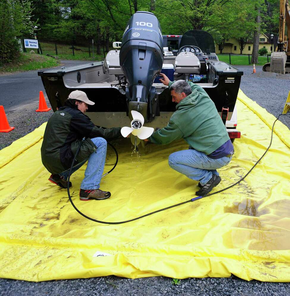 Mike Archambault, left, a vessel inspection technician checks over Carl Falco's, right, boat at Norowal Marina on Lake George on Thursday, May 15, 2014, in Bolton Landing, N.Y. Thursday was the first day that the various regional inspection stations were operating around Lake George. The mandatory boat inspection program is run by the Lake George Park Commission. The purpose of the inspections are to make sure that no boats are carrying invasive species into the lake. Boaters looking for information on the inspection sites and hours of operation can go to www.http://lgboatinspections.com. (Paul Buckowski / Times Union)