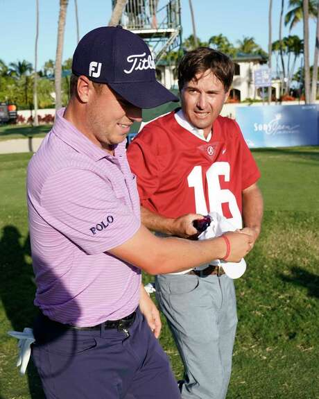 Justin Thomas, left, helps pairing partner Kevin Kiser put on an Alabama football jersey on the 17th tee during the first round of the Sony Open golf tournament Thursday, Jan. 11, 2018, in Honolulu. Kisner, who lost a bet to Thomas over the outcome of the college football championship game between Georgia and Alabama, had to wear the Alabama jersey during play on the 17th. Kisner is a former collegiate golfer at Georgia. (AP Photo/Marco Garcia) Photo: Marco Garcia, FRE / 2018