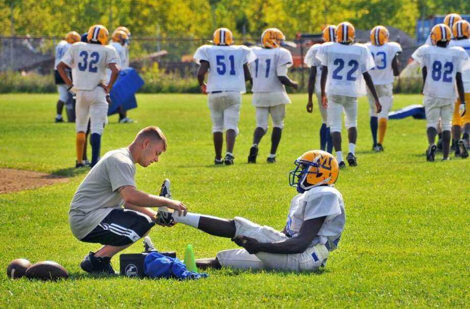 Bishop Maginn wide reciever Pierre Sandaire has his ankle taped up by JV coach Matt Ryan during football practice.  (John Carl D'Annibale / Times Union) Photo: John Carl D'Annibale / 00005259A