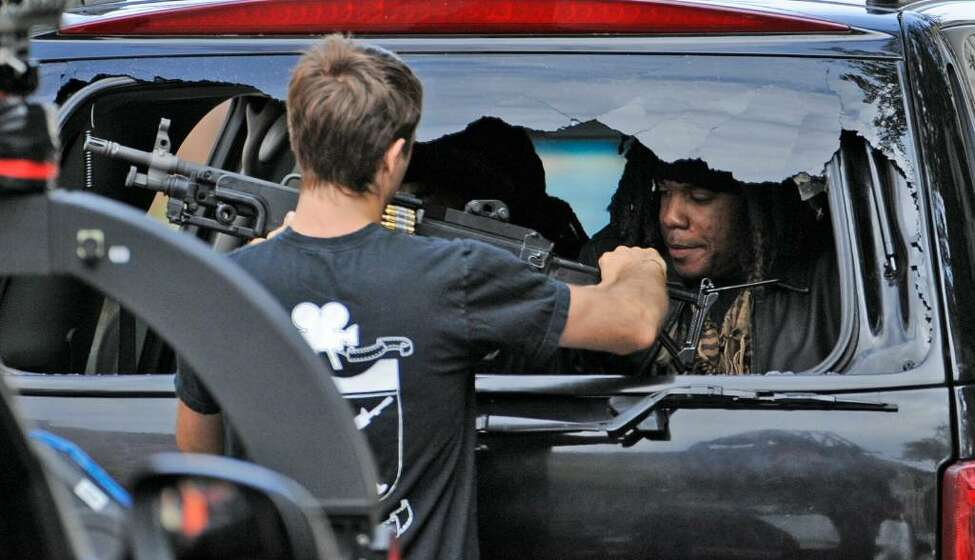 A weapons technician hands a machine gun to a stunt man in the rear of a Cadillac Escalade on Wednesday, Sept. 24, on Broadway in Albany. A film crew is shooting scenes for