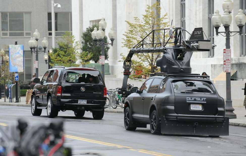 A Porsche Cayenne loaded with cameras chases a Cadillac Escalade on Wednesday, Sept. 24, on Broadway in Albany. It was the first day of shooting for the movie