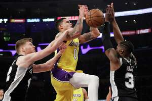 Los Angeles Lakers' Kyle Kuzma, center, is fouled by San Antonio Spurs' Davis Bertans, left, during the first half of an NBA basketball game Thursday, Jan. 11, 2018, in Los Angeles. (AP Photo/Jae C. Hong)