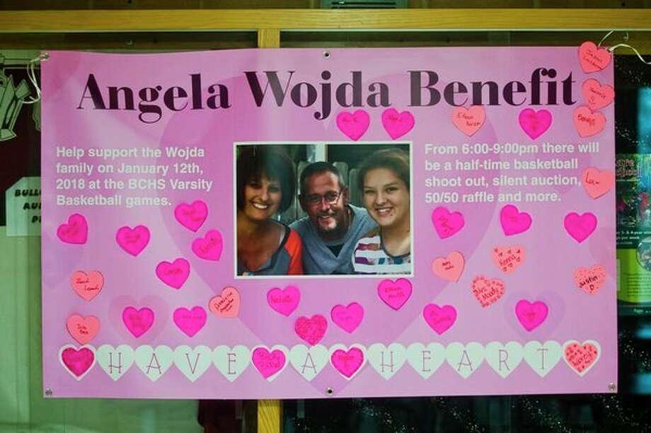 A poster for a benefit for the Wojda family hangs inside Bullock Creek High School on Thursday. (Katy Kildee/kkildee@mdn.net)