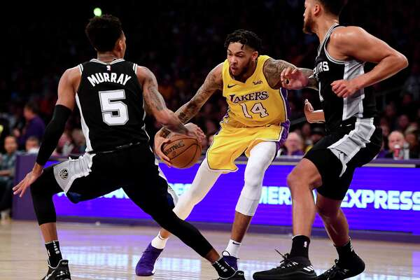 LOS ANGELES, CA - JANUARY 11:  Brandon Ingram #14 of the Los Angeles Lakers drives to the basket on Dejounte Murray #5 and Kyle Anderson #1 of the San Antonio Spurs during the first half at Staples Center on January 11, 2018 in Los Angeles, California.
