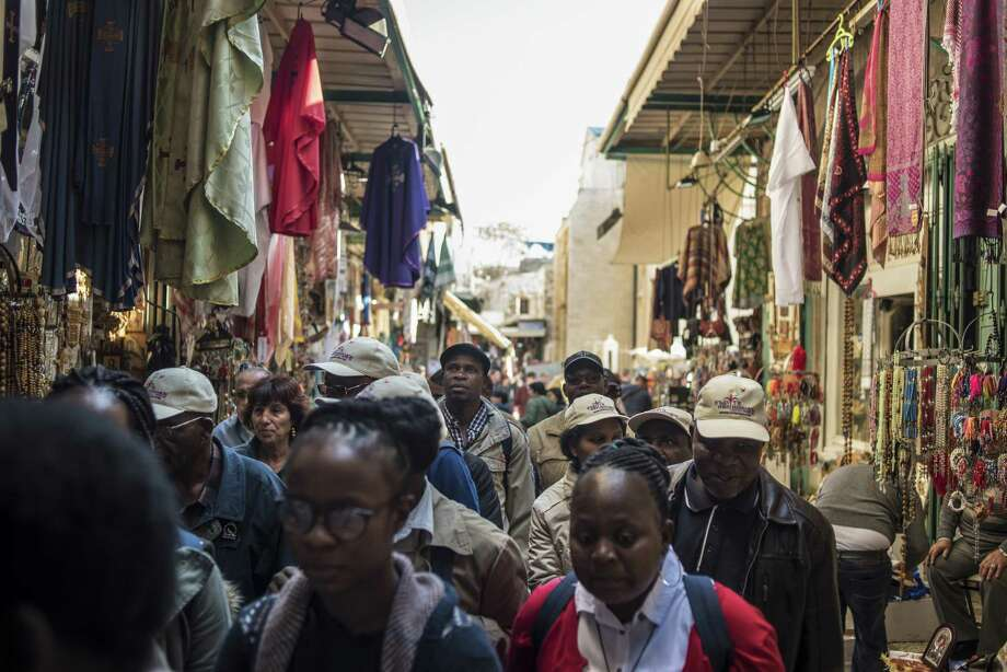 Tourists and locals walk through the Arab souq in the Christian quarter of the Old City in Jerusalem on Dec. 16, 2017. Photo: Bloomberg Photo By Geraldine Hope Ghelli. / © 2017 Bloomberg Finance LP