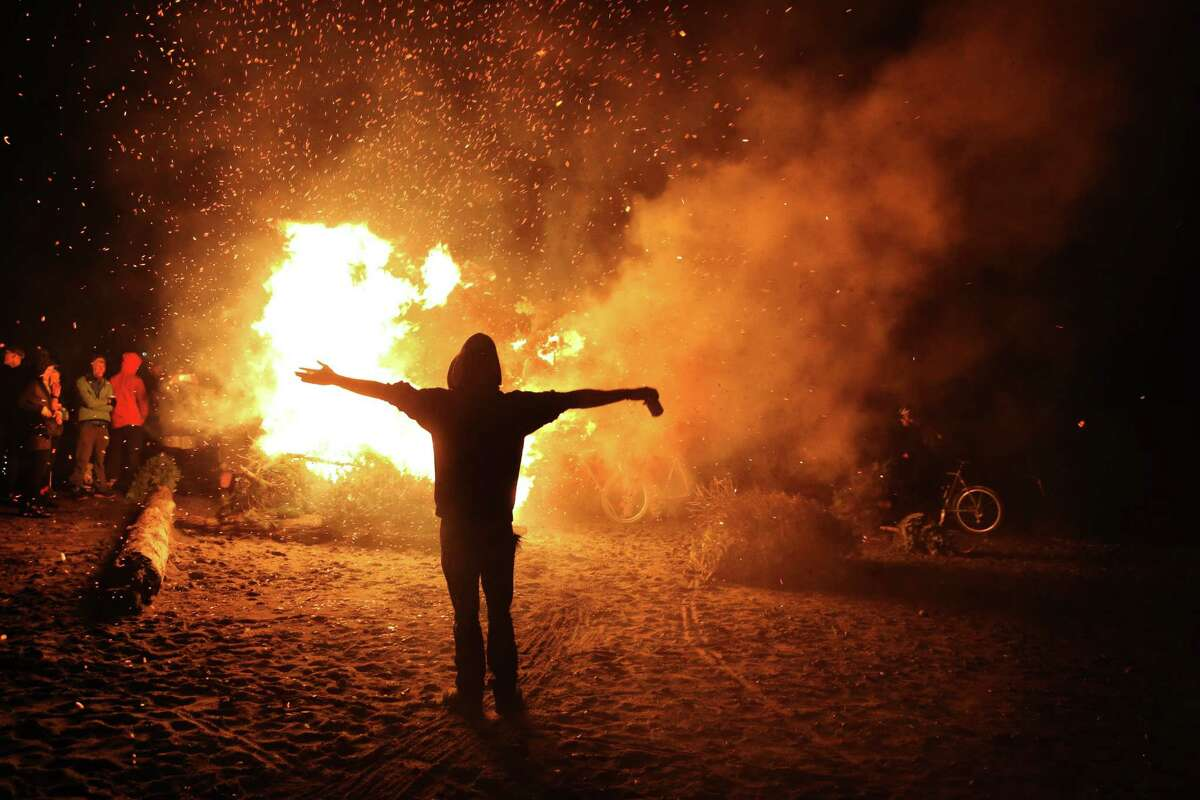 Scenes from the annual Point83 cyclist club Christmas tree burn, Thursday, Jan. 11, 2017 at Golden Gardens Beach Park. Participants bring their trees to the inferno, most via bicycle. The bonfire has become an annual tradition over the past decade.