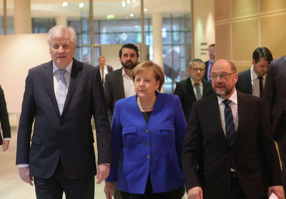 Horst Seehofer, leader of the Christian Social Union party ( left), German Chancellor Angela Merkel (center) and Martin Schulz, leader of the Social Democrat Party, arrive for a news conference following overnight coalition negotiations, at the SPD headquarters in Berlin on Jan. 12, 2018. Photo: Bloomberg Photo By Krisztian Bocsi. / © 2018 Bloomberg Finance LP