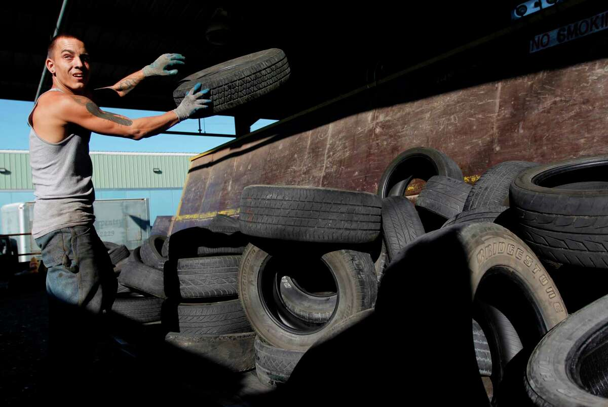 R.J, a temporary Liberty Tire Recycling employee, loads used tires on to the conveyer belt which will transport tires into the recycling process at Liberty Tire Recycling on Friday, Nov. 16, 2012, in Baytown. Liberty Tire Recycling is the largest tire processor in the country that shreds half of all the tires people discard every year, but they are now going to face competition from a new Houston plant that promises a cleaner, more modern recycling process. ( Mayra Beltran / Houston Chronicle )