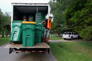Chris Mcglory rides a truck as he helps unload new Waste Management issued recycling trash and recycle bins on Mill Avenue, Thursday, Sept. 21, 2017, in Conroe. The Conroe City Council voted in April to not renew the city's contract with long-time provider Republic Services Inc.