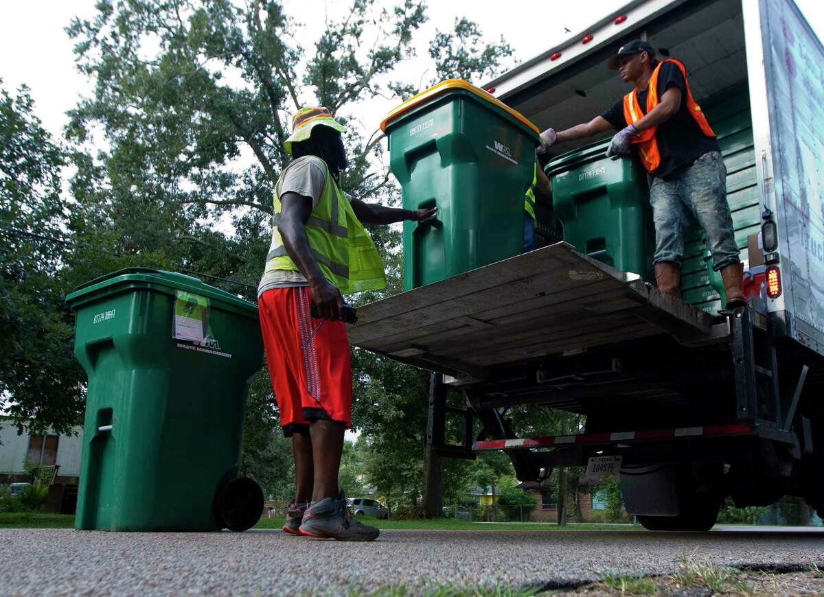 Workers help unload trash and recycling bins on Mill Avenue, Thursday, Sept. 21, 2017, in Conroe.