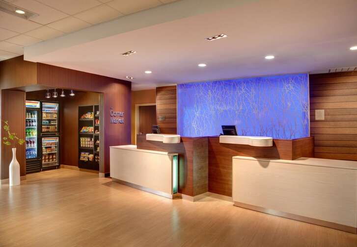 The lobby of the Fairfield Inn & Suites by Marriott is designed with a contemporary look and feel. A 24/7 Corner Market is stocked with snacks and drinks.