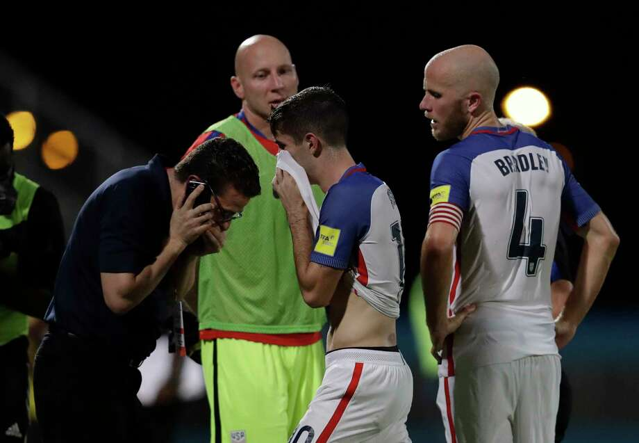 United States' Christian Pulisic, center, and his teammate United States' Michael Bradley, right, walk on the pitch after losing 2-1 against Trinidad and Tobago during a 2018 World Cup qualifying soccer match  in Couva, Trinidad, Tuesday, Oct. 10, 2017. (AP Photo/Rebecca Blackwell) Photo: Rebecca Blackwell, STF / Copyright 2017 The Associated Press. All rights reserved.