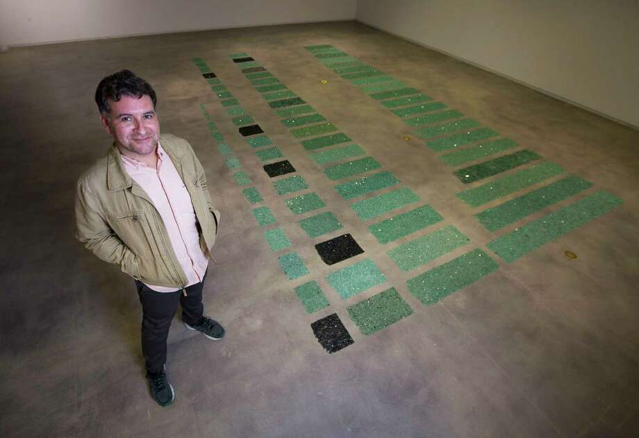 """Houston artistGabrielMartinezwith his piece """"The Long Poem of Walking,"""" a collection of broken automotive glass he has found moving through the city, which is at the center of his first solo museum exhibition at the Blaffer Art Museum at the University of Houston, Tuesday, Jan. 9, 2018, in Houston. ( Mark Mulligan / Houston Chronicle ) Photo: Mark Mulligan, Houston Chronicle / © 2018 Houston Chronicle"""