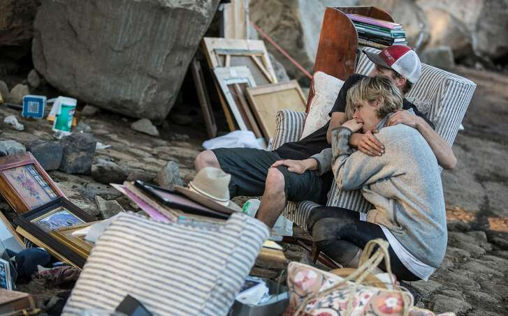 Travis Zehntner comforts Teresa Drenick, among the salvaged belongings of her sister Rebecca Riskin, who was killed in the mudslide along San Ysidro Creek in Montecito, Calif., on Thursday, Jan. 11, 2018. (Brian van der Brug/Los Angeles Times/TNS)