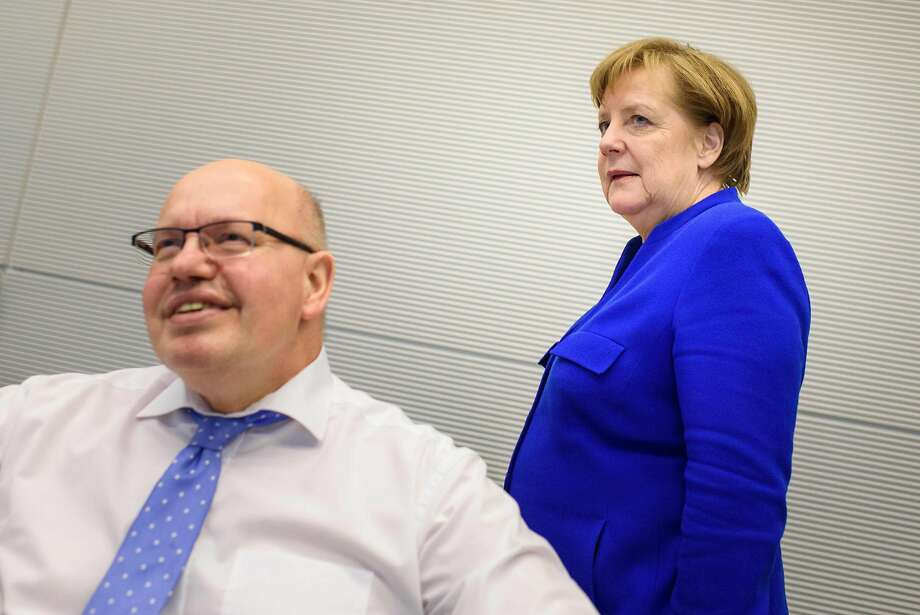 Chancellor Angela Merkel and interim Finance Minister Peter Altmaier arrive for party talks