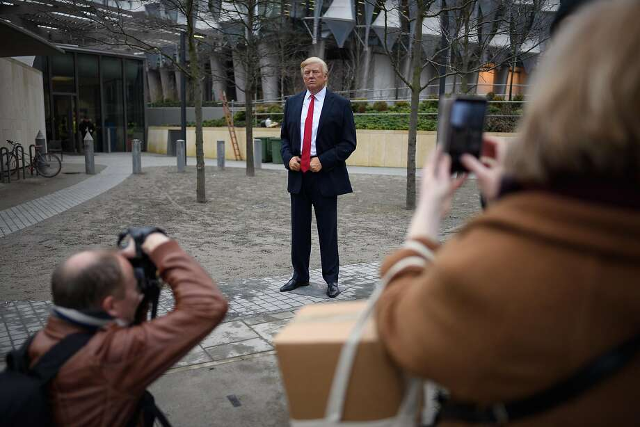 People take photographs of a model of President Trump from the Madame Tussaud's waxwork attraction outside the new U.S. Embassy in London. Photo: Leon Neal, Getty Images