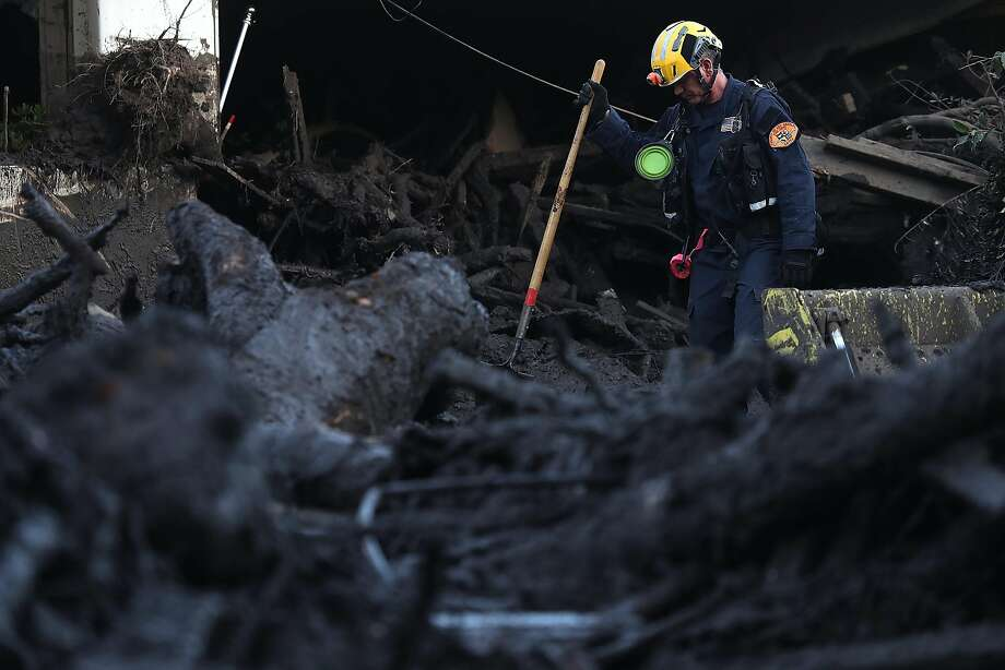 A rescue worker searches for possible mudslide victims in Montecito (Santa Barbara County). At least 18 people were killed. Photo: Justin Sullivan, Getty Images