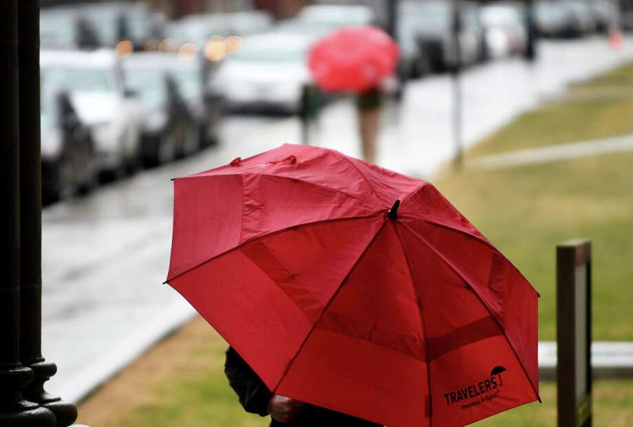 Umbrellas provided cover for a dash down State St. to the Capitol on Friday, Jan. 12, 2018, in Albany, N.Y. (Will Waldron/Times Union) Photo: Will Waldron, Albany Times Union / 20042656A