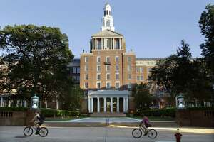 Bicyclists pedal past the Aetna headquarters in Hartford.