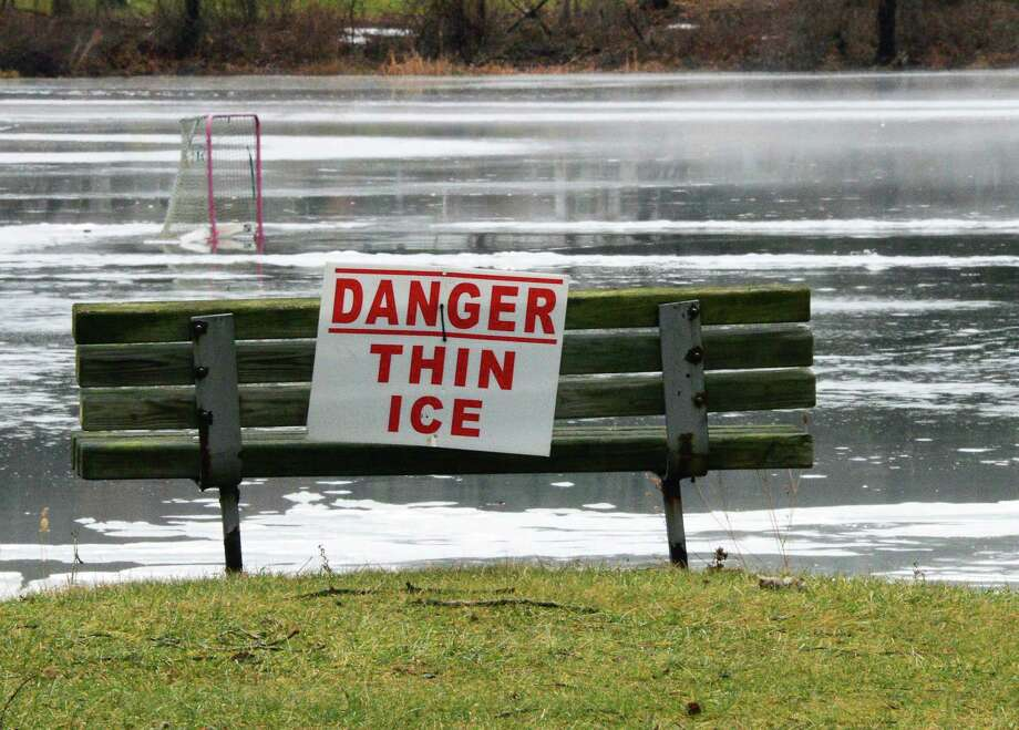 A Danger Thin Ice sign with the remnants of a pond hockey rink beyond Friday Jan. 12, 2018 in Clifton Park, NY.  (John Carl D'Annibale/Times Union) Photo: John Carl D'Annibale, Albany Times Union / 20042656A