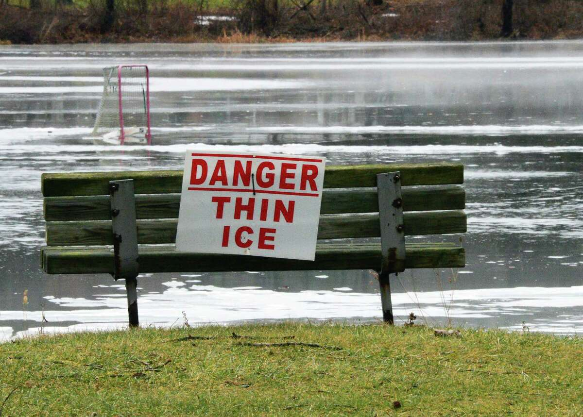A Danger Thin Ice sign with the remnants of a pond hockey rink beyond Friday Jan. 12, 2018 in Clifton Park, NY. (John Carl D'Annibale/Times Union)