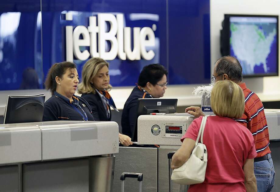 JetBlue Airways ticket agents assist passengers in Tampa. The airline is among the companies providing bonuses. Photo: Chris O'Meara, Associated Press