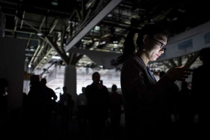 An attendee is illuminated by a mobile device during a power outage at the CES technology event in Las Vegas this past week. Many products at CES want to fill previously unimagined moments of your life with additional stimulation.