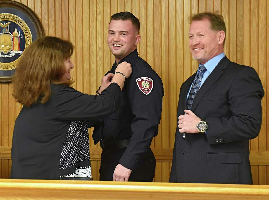 Ellen McNally attaches a police badge to her son Michael McNally after he is sworn in as Watervliet's newest police officer by Mayor Michael Manning, at right, at Watervliet City Hall Court on Friday, Jan. 12, 2018 in Watervliet, N.Y.  (Lori Van Buren/Times Union) Photo: Lori Van Buren, Albany Times Union / 20042638A