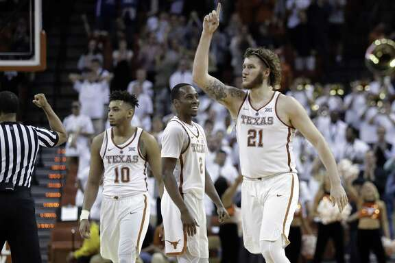 Texas' Eric Davis Jr. (10), Matt Coleman (2) and Dylan Osetkowski (21) celebrate during an NCAA college basketball game against TCU on Wednesday, Jan. 10, 2018, in Austin, Texas. Texas won in double overtime, 99-98. (AP Photo/Eric Gay)