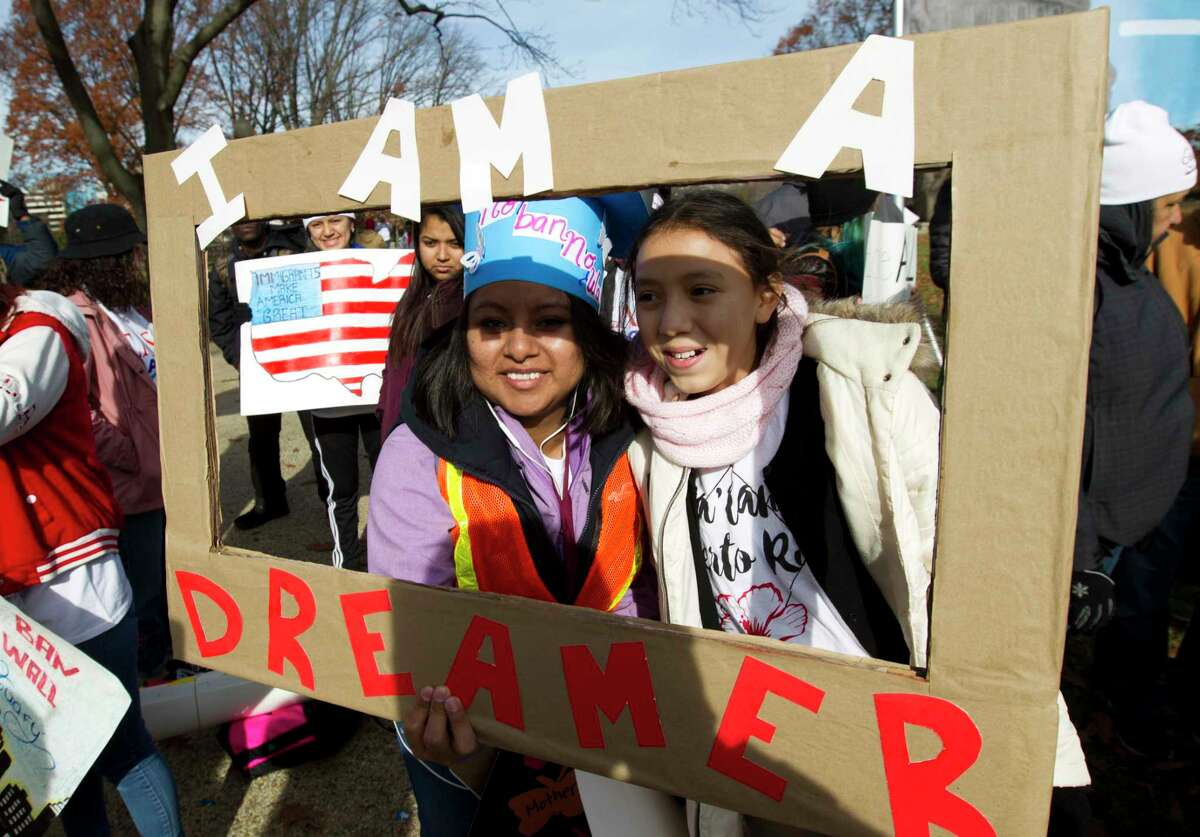 Demonstrators Karina Velasco, left, and Gabi Sanchez hold a sign during an immigration rally in support of the Deferred Action for Childhood Arrivals (DACA), and Temporary Protected Status (TPS), programs, on Capitol Hill in Washington, Wednesday, Dec. 6, 2017. ( AP Photo/Jose Luis Magana)