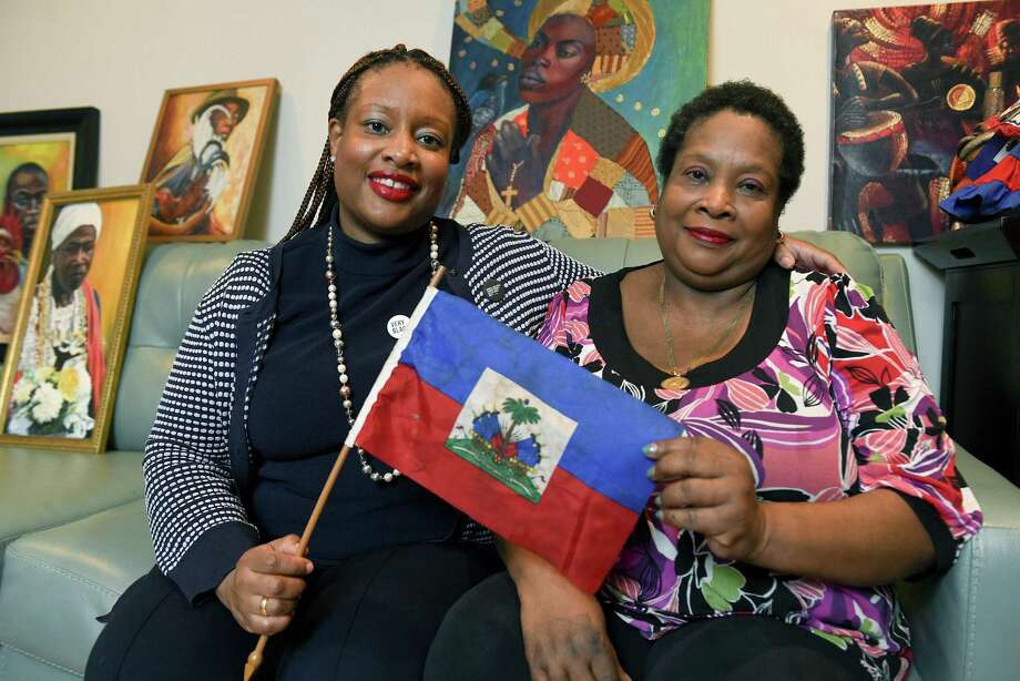 "Bianca Shinn-Desras is photograph on Friday, Jan. 12, 2018 with her mother, Bienne Domond-Shinn holding the flag of Haiti at there home in Stamford, Connecticut. Shinn-Desras was born and raised in Stamford. Her mother, Bienne Domond-Shinn, emigrated from Haiti in the 1970s. Desras said the Haitian community is upset by President Donald Trump's reported remarks about Haitians during immigration talks. ""It's an assault on a whole nation,"" she said. Photo: Matthew Brown / Hearst Connecticut Media / Stamford Advocate"