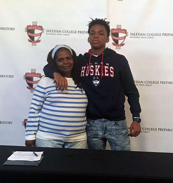 Salesian-Richmond's James Akinjo is joined by Roberta Stevenson, his grandmother, after signing his letter of intent to attend the University of Connecticut in November.