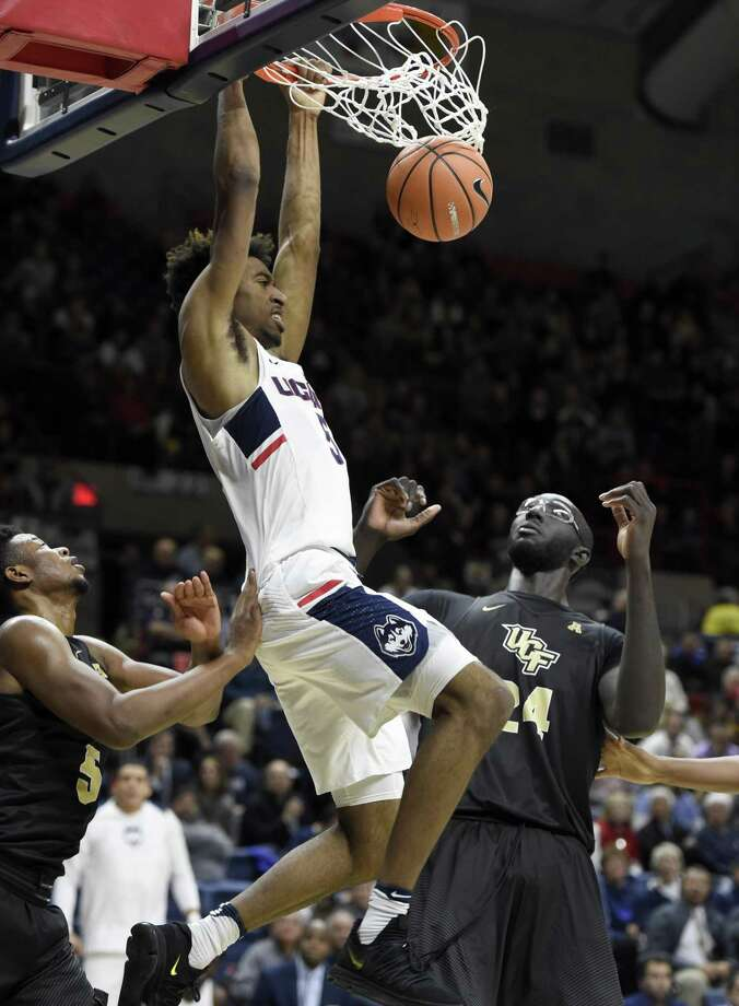 UConn's Isaiah Whaley dunks on a backdoor cut against UCF's Tacko Fall (24) in Storrs on Wednesday. Photo: John Woike / Hartford Courant / Hartford Courant