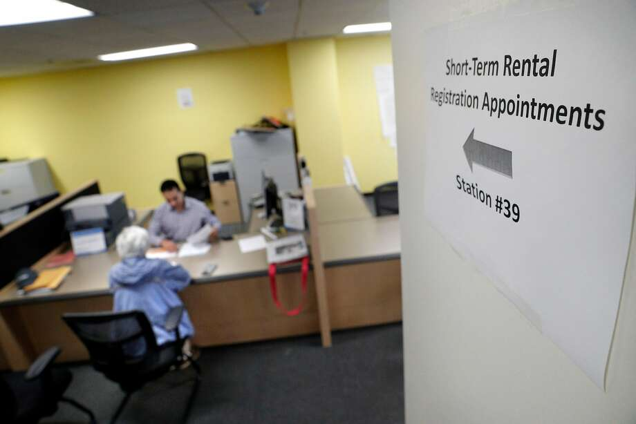 A sign points to the desk where Senior Analyst Omar Masry helps Marcy Lipton with her paperwork for hosting guests in her home at the Office of Short Term Rentals in San Francisco, Calif., on Wednesday, January 10, 2018. San Francisco residents who wish to host guests host guests  through Airbnb, VRBO or other homesharing services must register with SF by Jan. 16 or they will be penalized by the city. Photo: Carlos Avila Gonzalez, The Chronicle