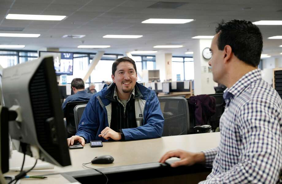 Gustav Choto (left) talks with Omar Masry, senior analyst at the short-term rental office. Hosts in San Francisco for Airbnb and other services must register properties by Tuesday. Photo: Carlos Avila Gonzalez, The Chronicle