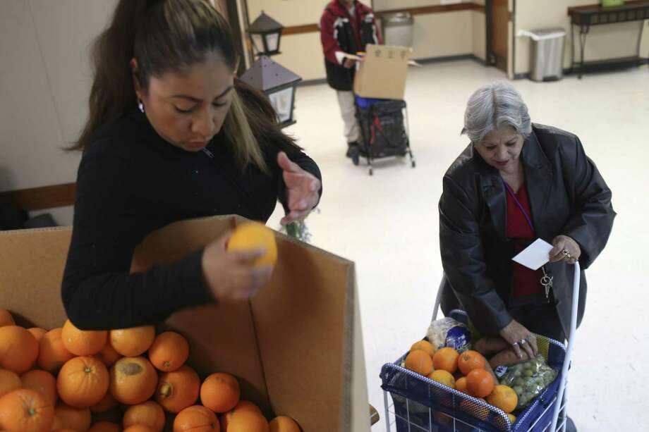 Michelle Cruz, 42, hands Angelita Elizondo, 68, oranges at the Last Chance Ministries Bread of Life Food Pantry Dec. 13, 2017. San Antonio has been ranked No. 1 in economic segregation. Photo: JERRY LARA /San Antonio Express-News / © 2017 San Antonio Express-News