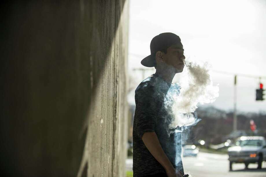 A teen smokes an e-cigarette in Peekskill, N.Y. A reader thinks the emphasis on restricting the sale of alcohol should be as great as on the focus on e-cigarettes. Photo: BRYAN THOMAS /NYT / Internal