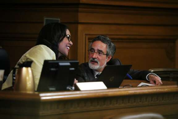 Supervisor President London Breed chats with Supervisor Aaron Peskin during a Board of Supervisors meeting at City Hall, in San Francisco, California on Tuesday, February 23, 2016.