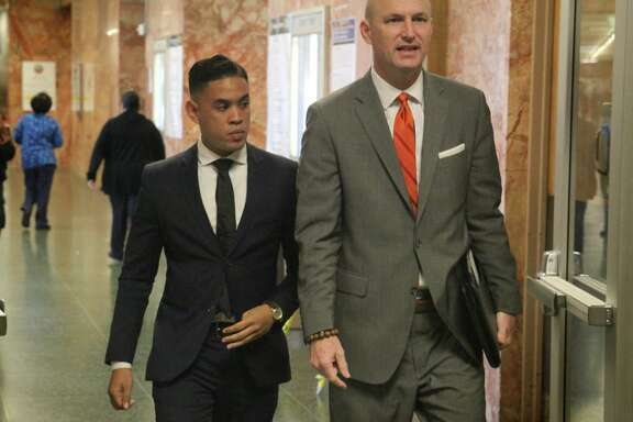 Justin McCall, left, arrives at the San Francisco Hall of Justice on Friday to face arraignment on two sex assault charges. He pleaded not guilty.