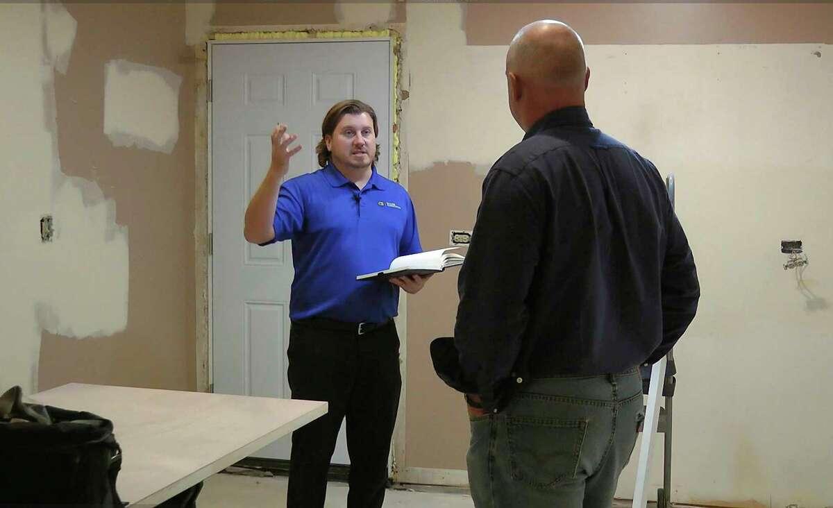 In this Nov. 17, 2017, photo taken from video, Billy Schuler, Best Buy in-home advisor, left, speaks with homeowner and customer Steve Frederick, at Frederick's home in Chicago. Schuler offered advice about speakers that can be adjusted from a smartphone. Best Buy has begun a free service in key markets where salespeople will sit with customers in their own homes and make recommendations on setting up a home office to designing a home theater system. (AP Photo/Teresa Crawford)