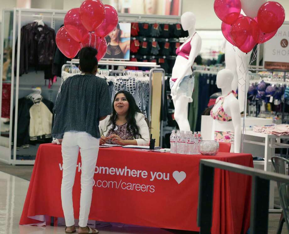 FILE - In this Friday, Oct. 13, 2017, file photo, Target human resources representative Critsina Lugo, seated, talks with a job seeker at a Target store in Dallas. Shifting shopper habits spell disruption for retail workers, who have new duties, different roles, or are fighting for customers. Some of the biggest retailers, like Walmart and Target, have made moves to increase pay in the face of low unemployment and competition for workers. (AP Photo/LM Otero, File) Photo: LM Otero, STF / Copyright 2017 The Associated Press. All rights reserved.