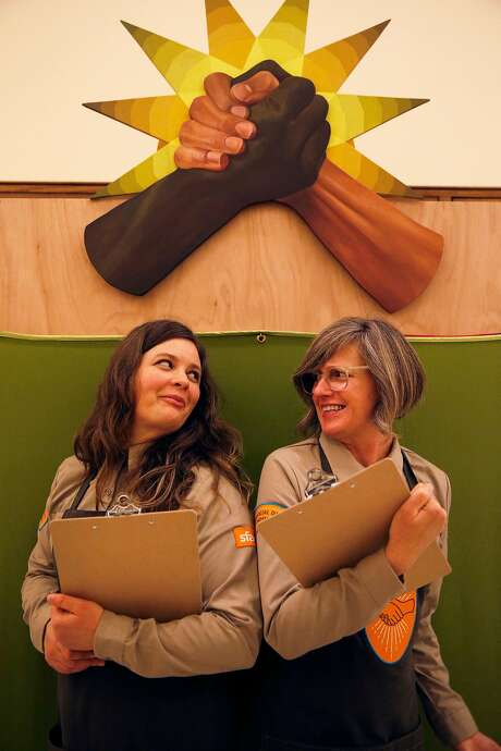 Hannah Ireland (left) and Alison Pebworth are collecting stories about shaking hands from people who come to the lobby of San Francisco City Hall. Photo: Jessica Christian, The Chronicle